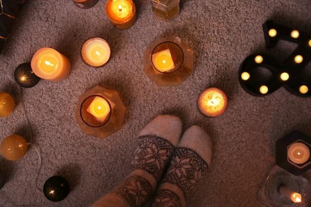 Donna in calzini caldi in piedi vicino a candele accese al chiuso, vista dall'alto