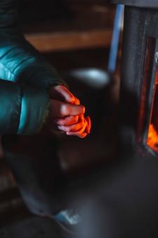 Donna in fase di riscaldamento vicino a un caminetto in una capanna