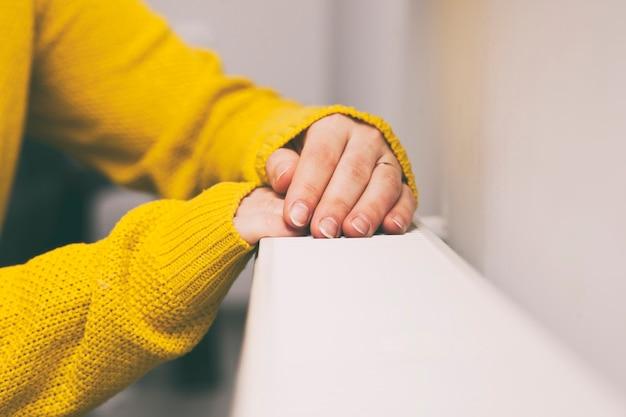 La donna si scalda le mani sul termosifone