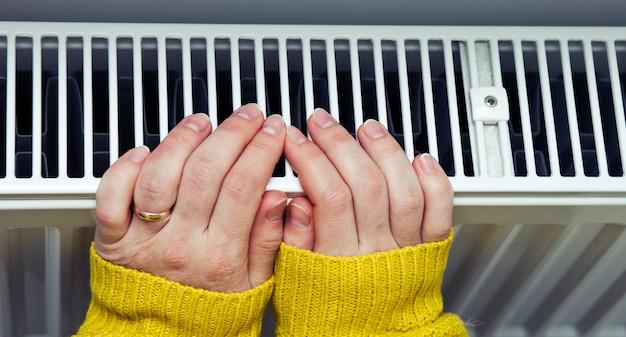 La donna si scalda le mani sul termosifone Foto Premium