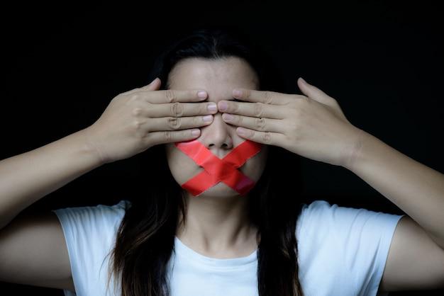 La donna stava avvolgendo la sua montatura con del nastro adesivo, concetto di libertà di parola, giorno umano giusto