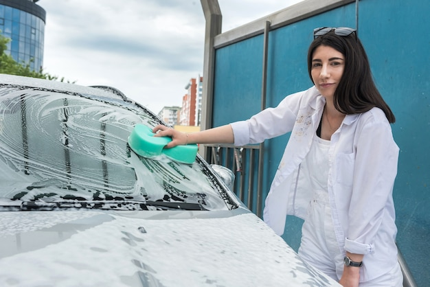 La donna lava l'auto con una spugna e schiuma. servizio auto di qualità. concetto di pulizia