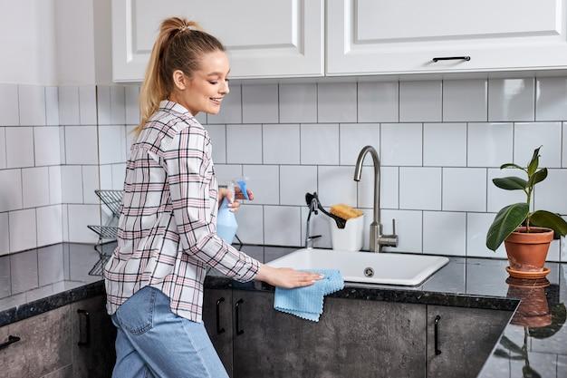 La donna lava il set da cucina di pulizia con uno straccio o un panno. servizio di pulizia professionale della casa. femmina caucasica nella cucina di pulizia dell'abbigliamento casual. vista laterale
