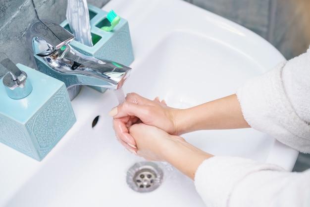 La donna si lava la mano nel lavandino del bagno