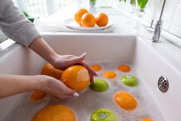 La donna che lava la mela, il pompelmo, l'arancia sotto il rubinetto nella cucina del lavandino, immergendo i frutti in acqua insaponata lava accuratamente dopo il negozio.