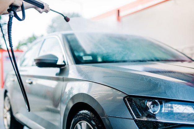 Donna che lava l'auto alla stazione di autolavaggio utilizzando una macchina per acqua ad alta pressione.
