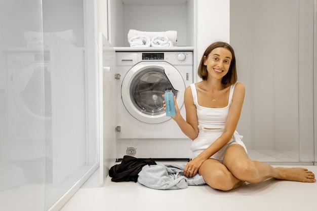 Donna che lava i panni con la lavatrice in bagno