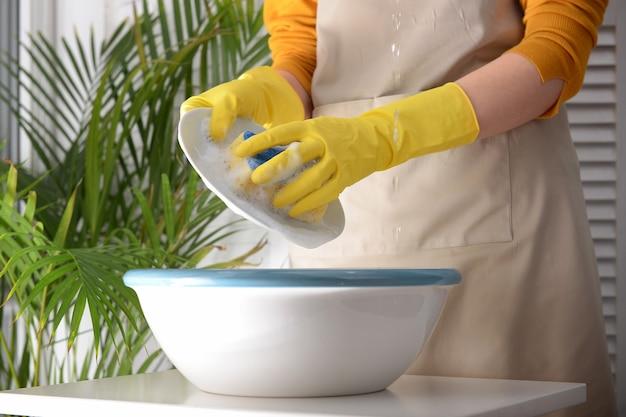 Donna che lava i piatti nella bacinella