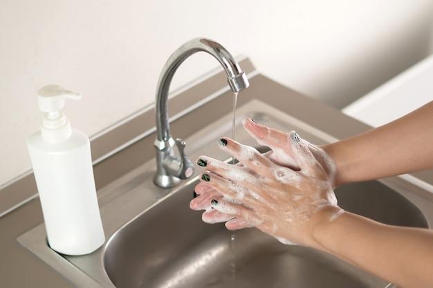 La mano di lavaggio della donna per la prevenzione del virus della corona le mani di lavaggio smettono di diffondere il concetto di igiene del coronavirus