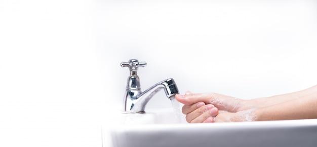 Mano di lavaggio della donna con schiuma di sapone e acqua di rubinetto in bagno.