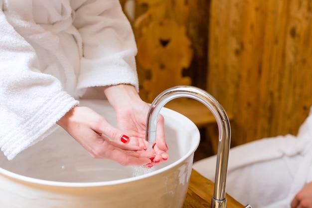 Donna che lava le mani al centro termale di benessere