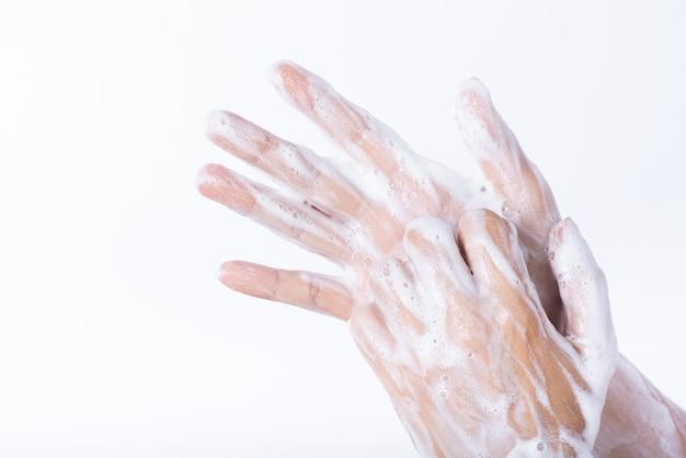 Mani di lavaggio della donna con sapone su fondo bianco. concetto di assistenza sanitaria.