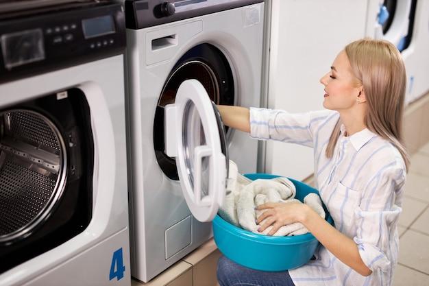 Donna in lavatrice che ordina vestiti puliti, facendo lavori domestici, donna tira fuori i vestiti dalla lavatrice, tenendo il bacino. vista laterale
