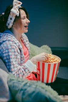 Donna che guarda film divertente sulla tv e che mangia popcorn sul sofà.