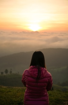 Donna che guarda l'alba da sola in cima alla collina