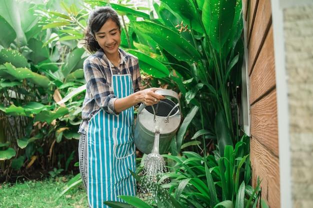 Donna che innaffia il suo giardino a casa