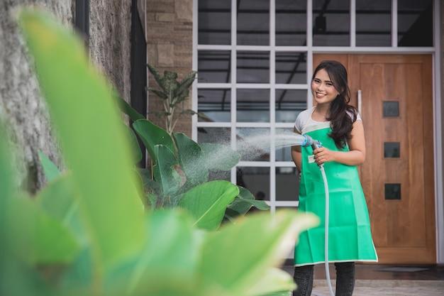 Donna che innaffia il suo giardino
