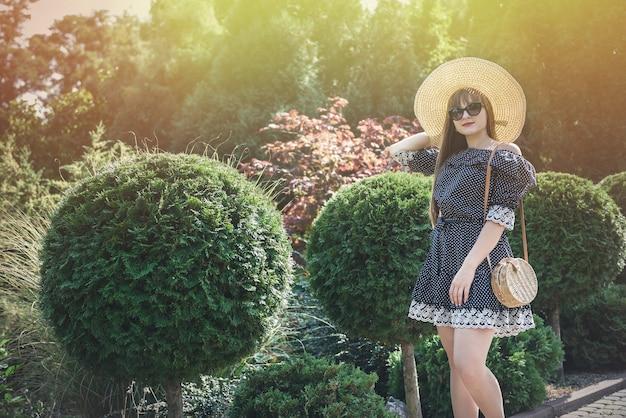 La donna indossa un abito blu nel giardino estivo, stile di vita