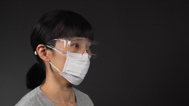 La donna indossa una maschera facciale e occhiali trasparenti su sfondo nero.
