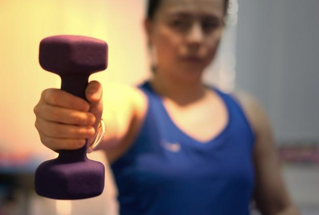 Donna indossare orologio sportivo tenere sollevamento manubrio una mano forza labbro per seno bicipite muscolo allenamento con pesi interni sfocatura sfondo