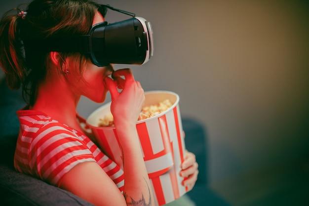 La donna indossa le cuffie vr e guarda i film con popcorn di notte. donna americana seduta sul divano con gli occhiali vr e guardare qualcosa mentre si mangia popcorn. interno