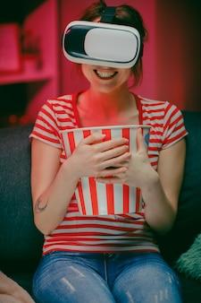 La donna indossa le cuffie vr e guarda i film con popcorn di notte. donna americana seduta sul divano con gli occhiali vr e guardare qualcosa mentre si mangia popcorn.