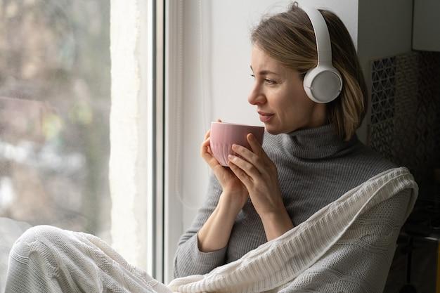 La donna indossa le cuffie wireless, ascolta la musica, seduto sul davanzale della finestra, guardando la finestra