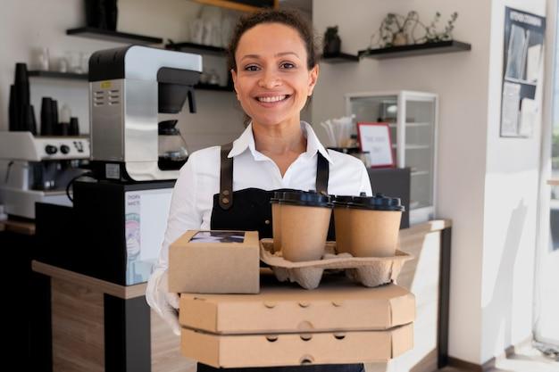 Donna che indossa un grembiule e tiene in mano cibo da asporto e tazze di caffè cup