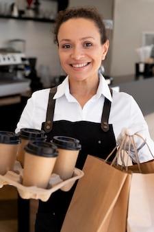 Donna che indossa un grembiule e tiene in mano dei sacchetti di carta con cibo da asporto e tazze di caffè