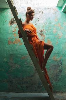 Donna che indossa un bel vestito lungo e vecchia scala in legno