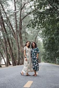 Donna che indossa un bellissimo abito lungo in piedi sulla strada sotto gli alberi verdi.