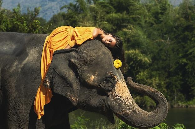 La donna che indossa un bellissimo vestito arancione sta cavalcando il potente elefante