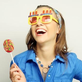 Donna che indossa i grandi occhiali da sole che tengono lecca-lecca