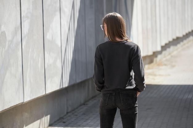 Donna che indossa felpa nera o felpa con cappuccio per mock up, logo o stampe di design con spazio libero per le strade della città.