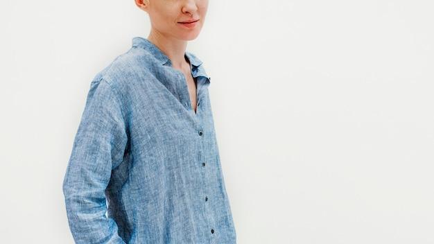 Donna che indossa una maglietta blu in piedi contro un muro bianco