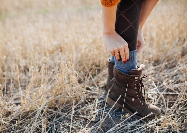 Donna che indossa stivali, calzini di regolazione, in un campo.