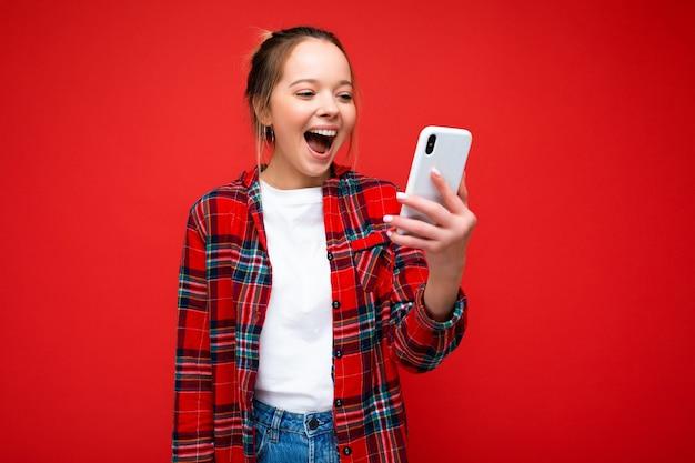 Donna che indossa abiti casual alla moda in piedi isolato sul muro con copia spazio tenendo e utilizzando il telefono cellulare guardando lo schermo del dispositivo.