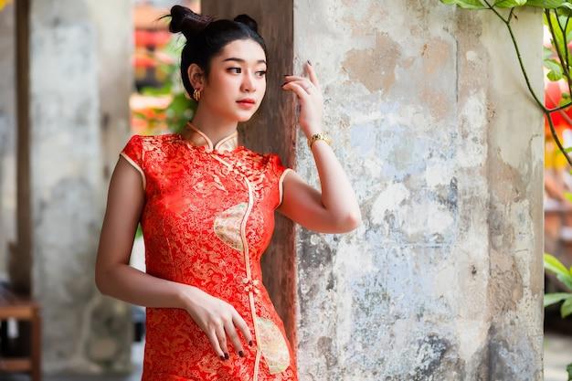 Una donna che indossa un cheongsam rosso cinese è in piedi in un corridoio