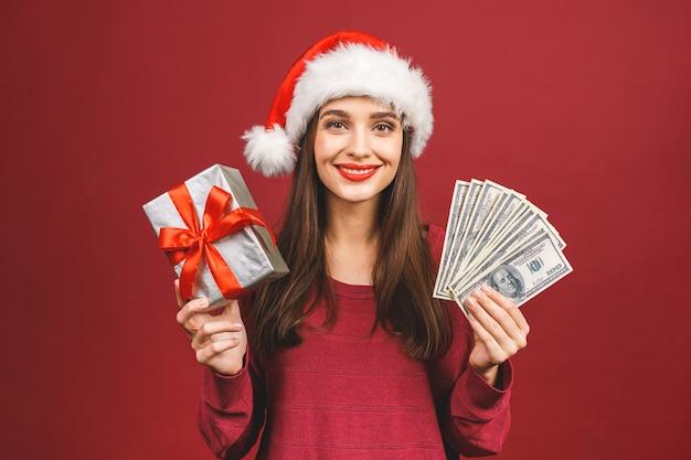 Donna che indossa il cappello di natale che tiene soldi e confezione regalo a sorpresa
