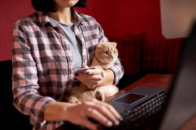 La donna che indossa uno stile comodo sta acquistando con carta di credito su un laptop nero che tiene un gatto