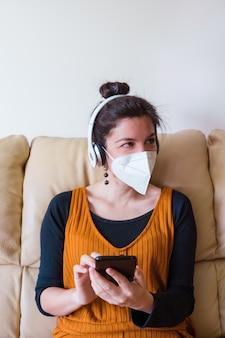 Donna che indossa la maschera per il viso chiamando un amico a casa. le persone infette da coronavirus nel divano di casa. stare a casa. malattia da virus pandemico covida 19.