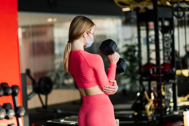 La donna che indossa la maschera per il viso esercita l'allenamento in palestra durante la pandemia del virus corona.