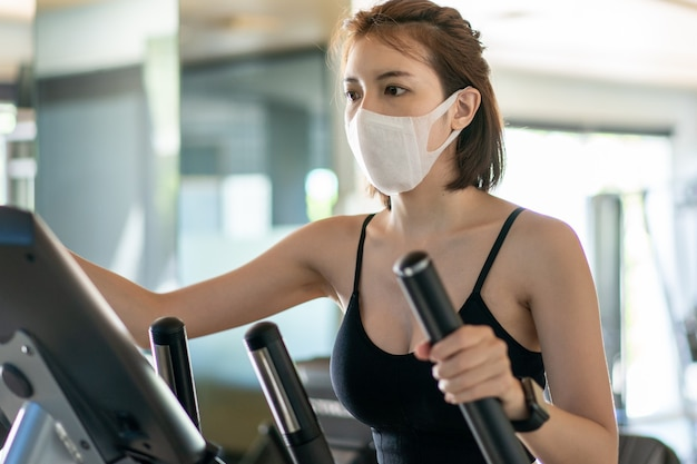 Donna che indossa la maschera per il viso, utilizzando una macchina ellittica in un centro fitness. durante la pandemia del coronavirus.
