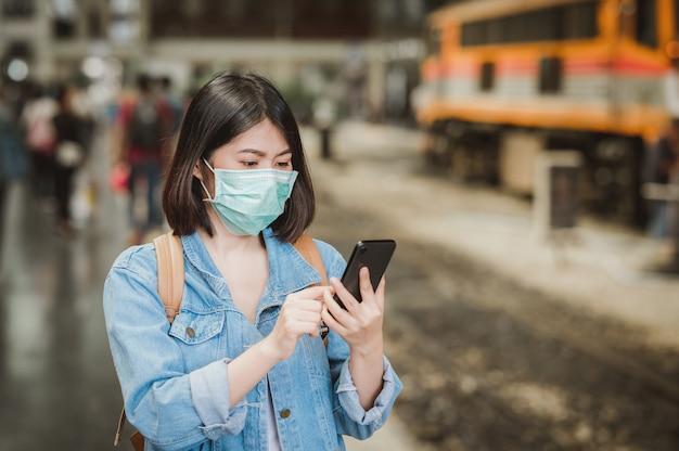 Donna che indossa una maschera viso utilizzando smartphone durante il viaggio
