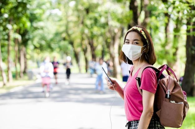 Donna che indossa una maschera per il viso con agitando le mani per salutare la sua amica e utilizza lo smartphone per ascoltare musica all'aperto in un parco verde lussureggiante
