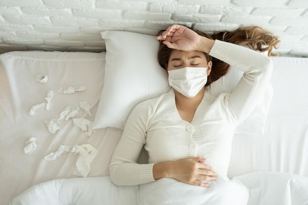 La donna che indossa una maschera protettiva per il viso sdraiata con un mucchio di tessuti sul letto ha la febbre di corona virus 2019 o covid-19