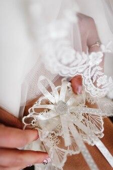 Donna che indossa una giarrettiera sulla gamba. la sposa tiene in mano una giarrettiera smarrita nella camera d'albergo. concetto di matrimonio preparazione mattutina.