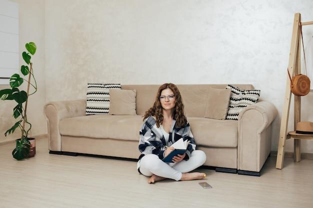 Donna con gli occhiali che tiene il blocco note seduta sul pavimento vicino al pullman