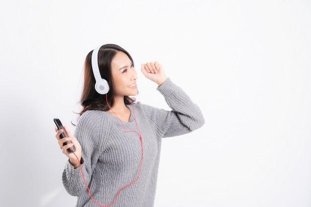 La donna che indossa un maglione grigio sta mentendo e sta ascoltando la musica che indossa le cuffie bianche di musica isolate su bianco.