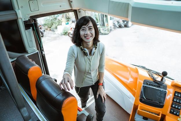 Una donna che indossa le cuffie sorride attraverso la porta dell'autobus mentre sale sull'autobus